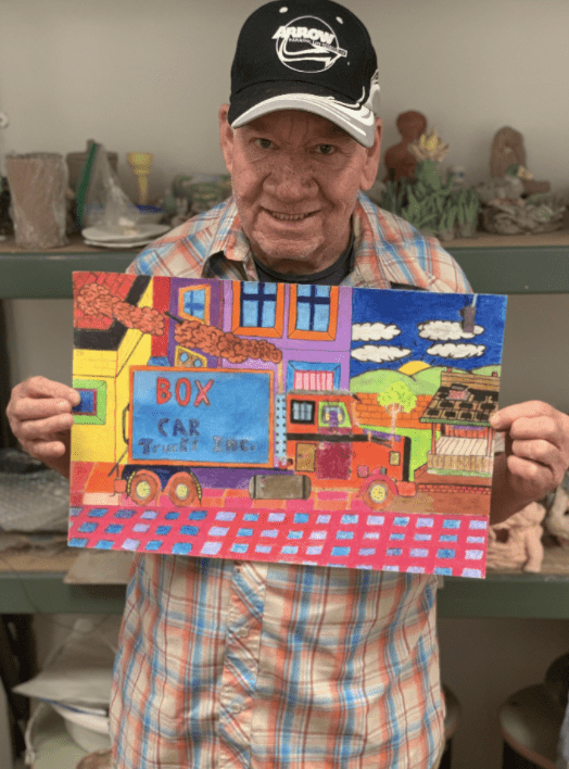 (An artist holding his artwork and smiling. He is an elder white man wearing a black baseball cap and a plaid shirt, with blue, orange and light orange colors. He is holding a drawing he made of a vibrantly colored box car.)