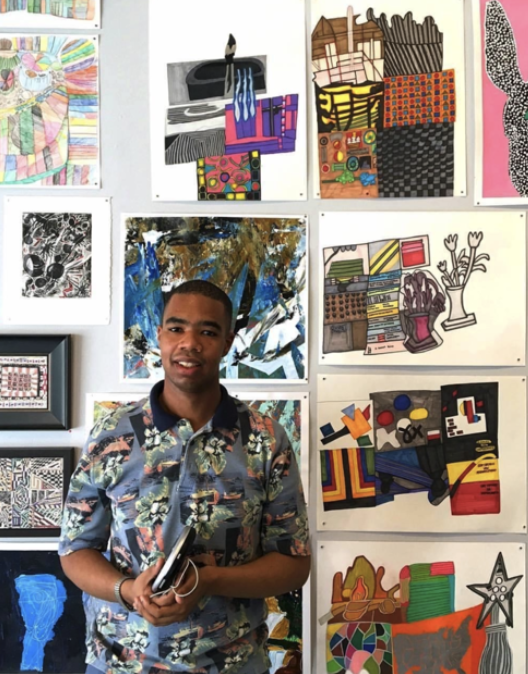 The image is a photograph of a man standing in front of 11 artworks. He is wearing a colorful patterned shirt with a black collar. (provided by Tierra and the artist