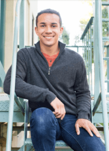 (The actor is young African American man, smiling at the camera, wearing a charcoal gray quarter-zip sweater, reddish-orange shirt underneath and blue jeans)